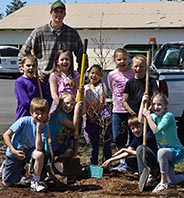 Linemen Tyler with kids planting trees outside