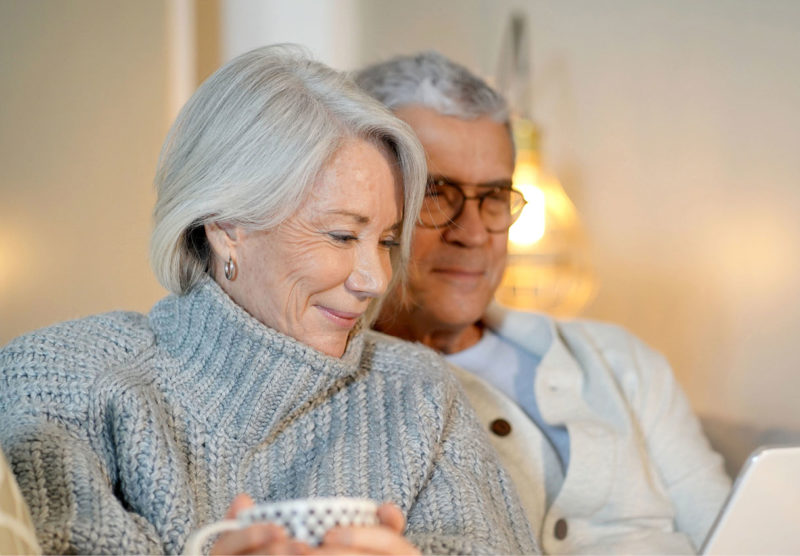 older man and woman sitting on couch together