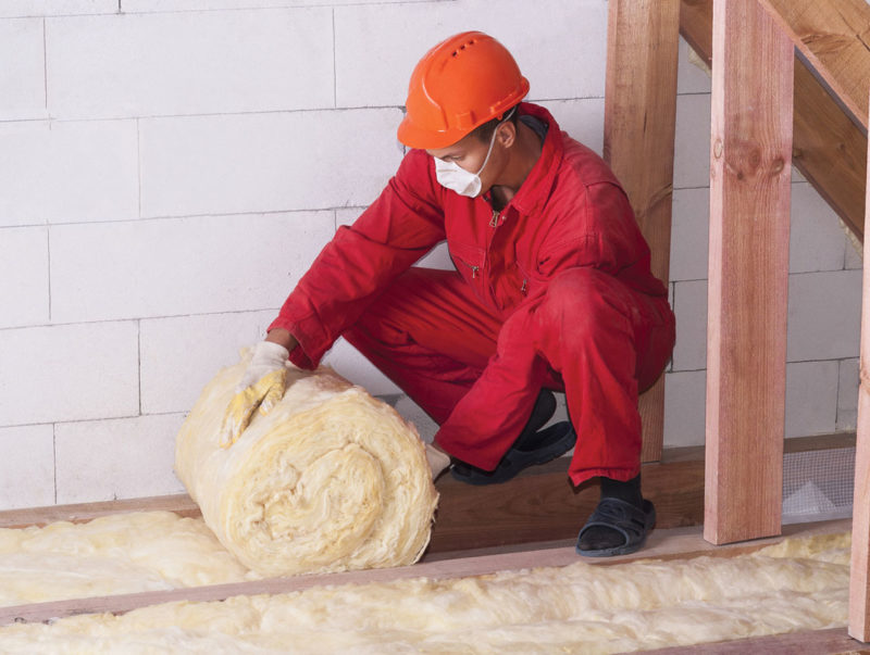 man rolling out insulation in attic