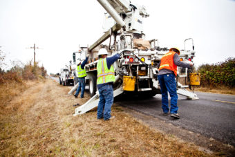 Linemen on side of road with their truck