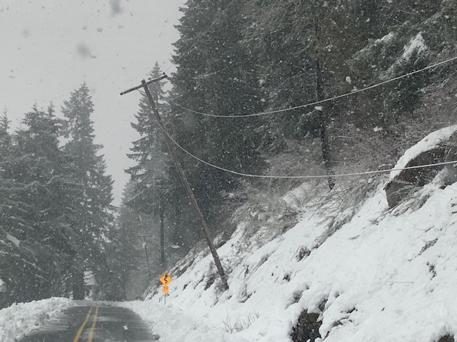 Leaning Power Pole on side of road with snow